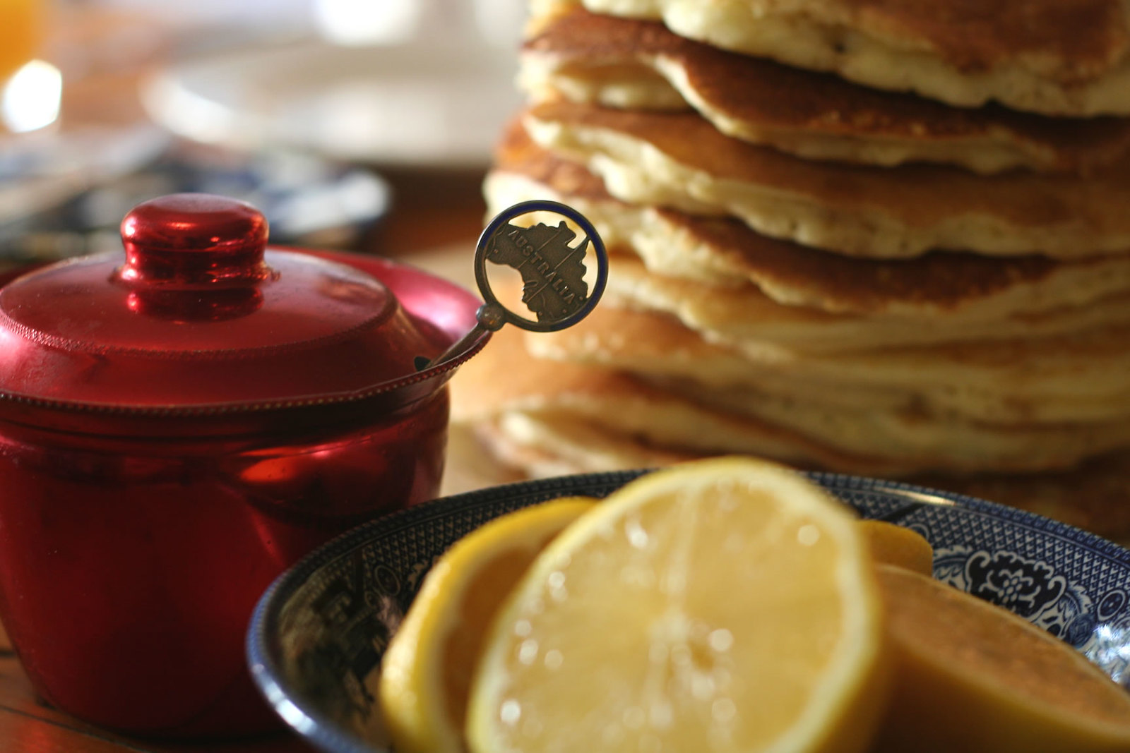 A bowl of lemons, a red teapot, and a stack of lemons sitting on a table